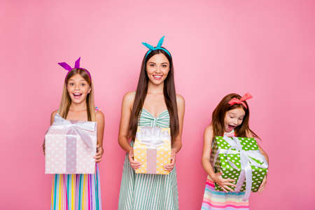 Portrait of cheerful siblings with headbands on long hairdo get giftbox for 8-march wearing skirt dress isolated over pink background