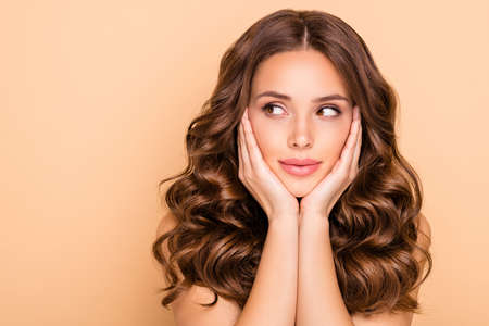 Close-up portrait of her she nice-looking attractive lovely feminine calm wavy-haired girl touching cheeks looking aside copy space advertisement isolated over beige pastel color background