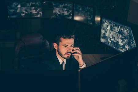 Portrait de son il gentil et séduisant spécialiste de la propriété privée de sécurité sérieuse supervisant un panneau de technologie informatique à distance appelant l'employeur fournissant des informations Web en ligne sur le poste de travail Banque d'images