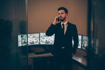 Portrait de son homme séduisant, sérieux, séduisant, élégant, élégant et imposant, supervisant le quart de nuit du panneau à distance en ligne, parlant à son partenaire au poste de travail
