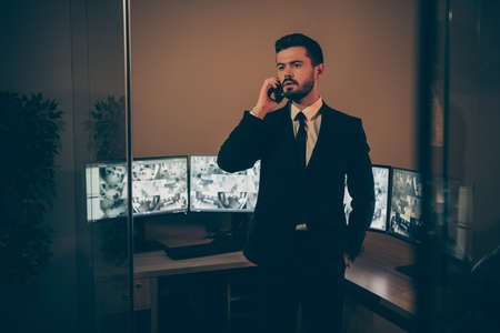 Portrait of his he nice attractive serious professional experienced stylish imposing man supervising online remote panel night shift talking to partner at work place station