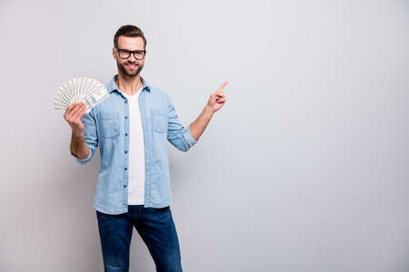 Photo of handsome guy holding fan of usa money dollars successful freelancer direct finger empty space advising nice credit offer wear specs denim outfit isolated grey color background