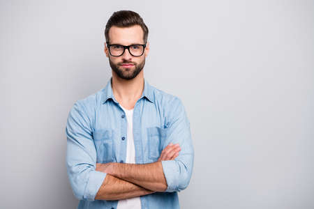 Photo of attractive guy serious looking young promoted boss chief hands crossed self-confident wear specs casual denim outfit isolated grey color background