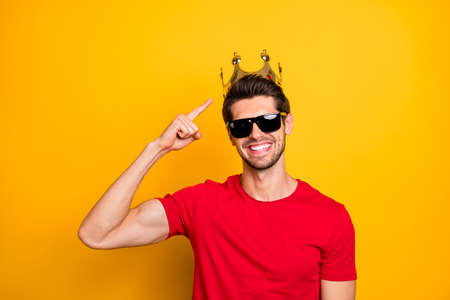 Look i best. Positive cheerful guy enjoy fun prom party event win gold tiara point index finger boast wear red t-shirt isolated over yellow color background Standard-Bild