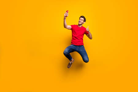 Full size photo of cheerful brown hair guy enjoy spring time holidays jump make selfie show thumb-up gesture recommend journey wear red t-shirt denim jeans isolated yellow color background
