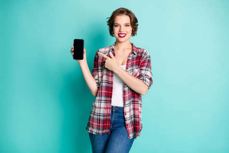 Portrait of positive cheerful girl promoter point index finger on smartphone present sales discount modern technology wear casual style clothing isolated over turquoise color background