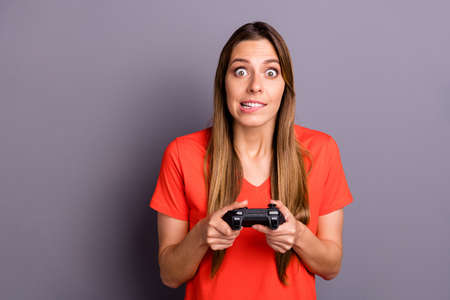 Portrait of addicted funky girl gamer play want win race speed game feel nervous bite lips wear good looking outfit isolated over grey color background