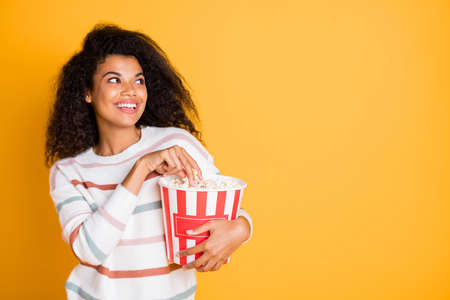 Photo portrait of cheerful funky excited girl enjoying tasty popcorn and watching favorite soap opera isolated bright color with copyspace