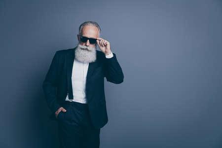 Portrait de son homme aux cheveux gris arrogant sérieux, séduisant, chic, élégant, élégant, vêtu d'un smoking touchant des spécifications isolées sur fond de couleur pastel gris foncé Banque d'images