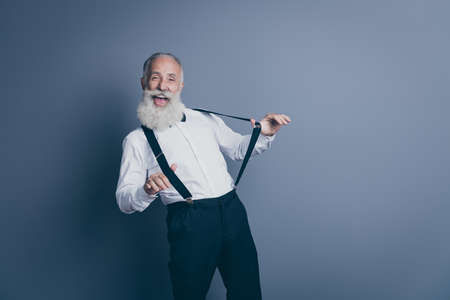 Portrait of his he nice attractive crazy cheerful cheery funny funky gray-haired man pulling suspenders clothes clothing having fun isolated over dark grey pastel color background