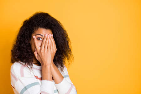 Close-up portrait of her she nice attractive lovely funny girlish wavy-haired girl hiding face in palms spy on peek isolated over bright vivid shine vibrant yellow color background 版權商用圖片