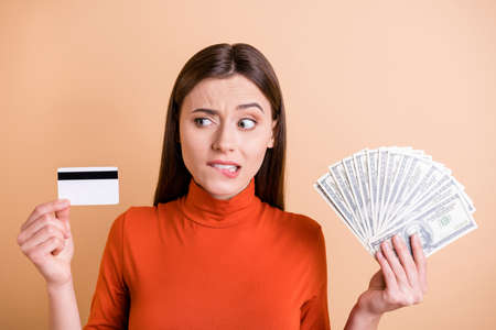 Photo of charming beautiful sad upset girlfriend looking suspiciously at credit card without understanding how it works holding money cash with hands inred turtleneck isolated beige color background 版權商用圖片