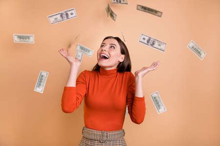 Photo of cheerful cute nice charming attorney earning large salary standing in cash rain wearing red turtleneck isolated over beige pastel color background