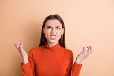 Close-up portrait of her she nice attractive sullen gloomy frustrated wild straight-haired girl expressing rage resentment offense isolated over beige pastel color background Stock Photo