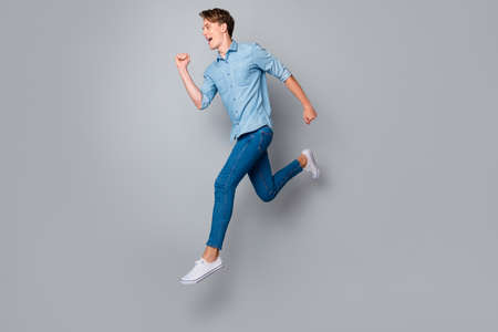 Full length profile side photo of enthusiastic guy jump run want hurry buy black friday bargains wear casual style clothing sneakers isolated over grey color background