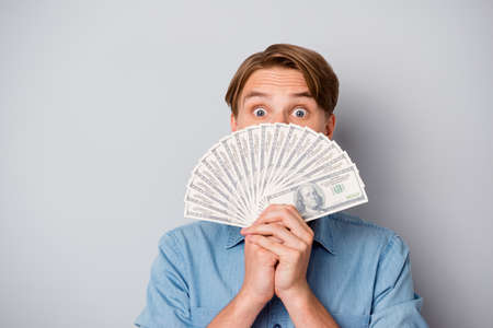 Close up photo of amazed funky guy win casino lottery jackpot hide his face with money fan impressed about his profit wear good looking outfit isolated over grey color background Zdjęcie Seryjne