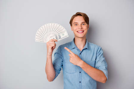 Portrait of positive cheerful guy hold money fan point index finger recommend credit bank deposit show his lottery casino win savings wear trendy outfit isolated over grey color background