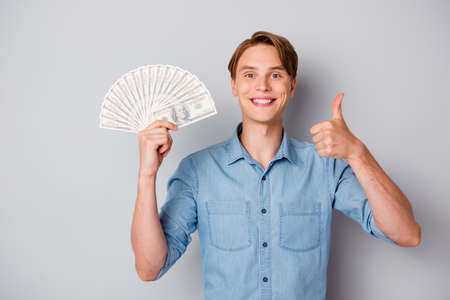 Portrait of positive content guy get million dollars hold money fan credit bank enjoy profit show thumb up recommend ads wear trendy outfit isolated over grey color background Reklamní fotografie