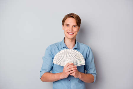 Portrait of positive cheerful guy get milllion dollars in credit bank hold money fan savings wear good looking clothing isolated over grey color background