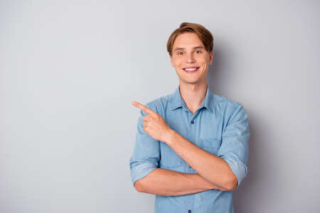 Portrait of confident cool guy promoter point index finger copypace pick tips ads promotion wear good look outfit isolated over grey color background