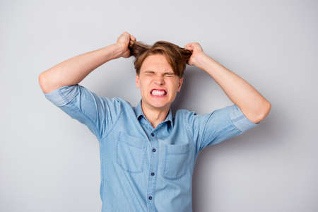 Portrait of frustrated outraged evil guy have lots of work routine lose temper feel exhausted hold his haircut close eyes wear stylish clothes isolated over grey color background