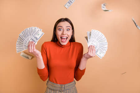 Portrait of her she nice attractive lovely cheerful cheery crazy glad straight-haired girl holding throwing large sum of money budget isolated over beige pastel color background