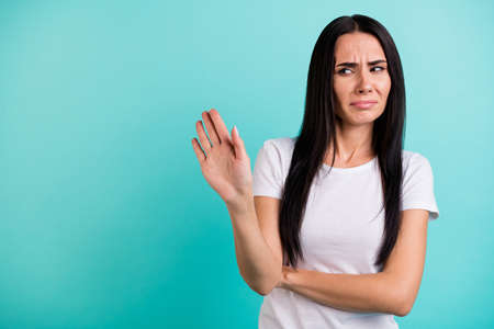 Photo of discontented casual woman gesturing with her palm to stop moving towards her grimacing in being disgusted isolated vivid teal color background