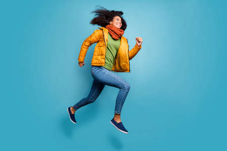 Full size profile photo of pretty dark skin lady jumping high rushing shopping store discounts wear overcoat jeans green sweater scarf isolated blue color background