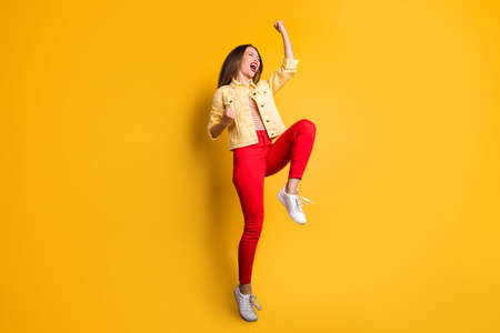 Full length body size photo of cheerful positive cute nice woman wearing red pants white sneakers jumping isolated vivid color background