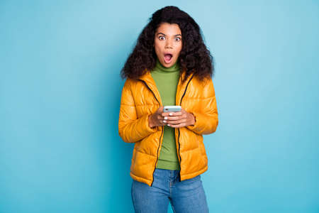 Photo of shocked dark skin curly lady open mouth holding telephone not believe eyes negative comments wear yellow overcoat jeans sweater isolated blue color background