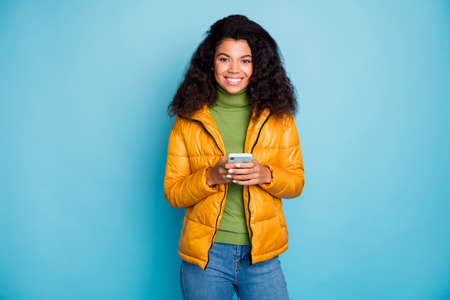 Photo of charming dark skin wavy lady holding telephone checking subscribers good mood wear yellow spring overcoat jeans green sweater isolated blue color background