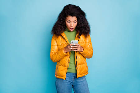 Photo of dark skin curly lady open mouth holding telephone hands not believe eyes negative comments wear yellow overcoat jeans sweater isolated blue color background