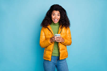 Photo of funny dark skin lady open mouth holding telephone hands enjoy new blog followers wear yellow spring overcoat jeans sweater isolated blue color background