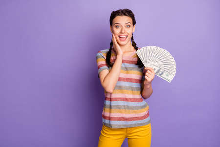 Photo of beautiful lady holding bucks rich young girl freelancer not believe big salary hand on cheek wear striped t-shirt yellow trousers isolated purple color background