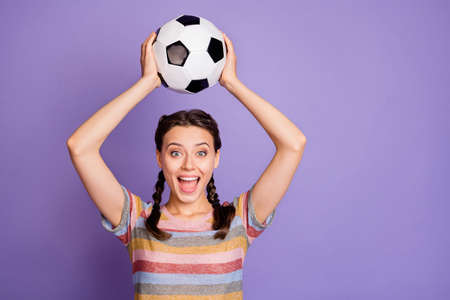 Portrait of excited funky teenager girl hold soccer ball support her team play world cup match win victory scream wow omg wear youth modern clothes isolated over violet color background Stock Photo