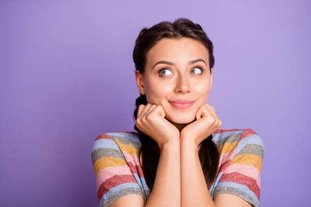 Close-up foto van geweldige schattige dame hand in hand onder de kin op zoek naar lege ruimte dromer stel je voor dat vlucht slijtage casual gestreept t-shirt geïsoleerde paarse kleur achtergrond