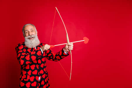 Portrait de son il gentil attrayant rêveur gai gai gars aux cheveux blancs tirant flèche match de mariage faire des sentiments fée isolé sur fond de couleur rouge vif brillant éclatant