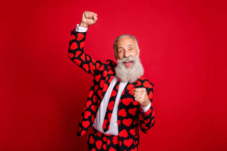 Photo of funky mature guy amour cupid character role raising fists, excited party beginning wear stylish hearts pattern suit costume shirt tie isolated vivid color background Фото со стока