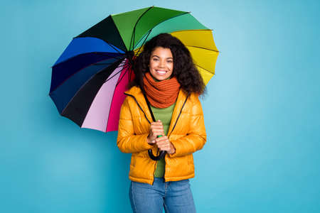 Photo of beautiful dark skin wavy lady good autumn weather outside walk street with umbrella wear yellow coat jeans green sweater knitted scarf isolated blue color background