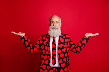 Photo of funky aged handsome man amour role holding open palms offer two sale products demonstrating novelty wear hipster hearts pattern suit blazer tie isolated red color background