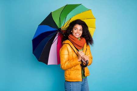 Photo of beautiful dark skin wavy lady good winter weather walk street hold umbrella look empty space wear yellow coat jeans sweater scarf isolated blue color background