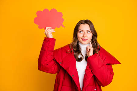 Photo of charming pretty lady holding empty paper cloud have creative idea to fill it finger on cheek clever person wear red winter overcoat isolated yellow color background