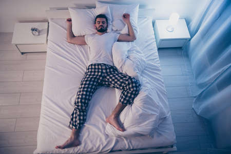 Top above high angle view of his he nice attractive sleepy drowsy guy lying on bed fallen asleep good life lifestyle at night late evening home illuminated room flat house Banque d'images