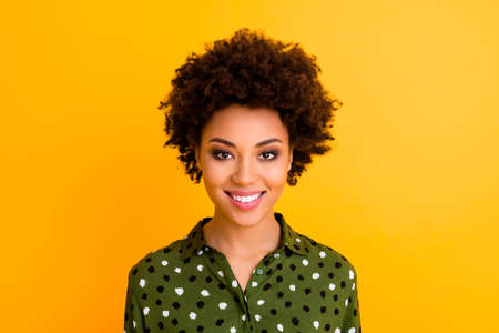 Photo of pretty dark skin wavy lady toothy beaming smiling positive good mood easy-going person wear green dotted shirt blouse isolated yellow color background Banco de Imagens