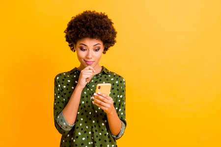 Photo of beautiful funny dark skin wavy lady hold telephone hands read good youth news look screen interested arm on chin wear green dotted shirt isolated yellow color background