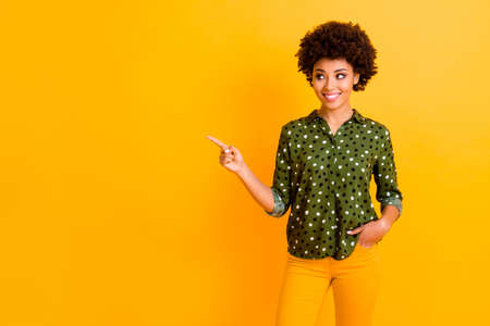Portrait of stylish positive afro american girl promoter point index finger copy space demonstrate adverts suggest select sales promo wear trendy outfit isolated over shine color background Banco de Imagens