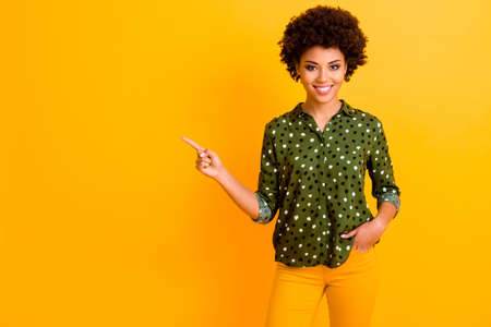 Portrait of confident cool afro american girl point index finger copy space present ads recommend promo wear stylish pants isolated over shine color background
