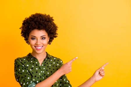 Foto di una donna ondulata con la pelle scura a trentadue denti divertente indica le dita spazio vuoto consigliando all'acquirente nuovo prodotto prezzo basso indossare camicia verde alla moda punteggiata camicetta isolato colore giallo sfondo