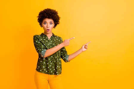 Photo of funny dark skin curly lady open mouth indicate fingers empty space show unbelievable low prices wear trendy green dotted shirt pants isolated yellow color background