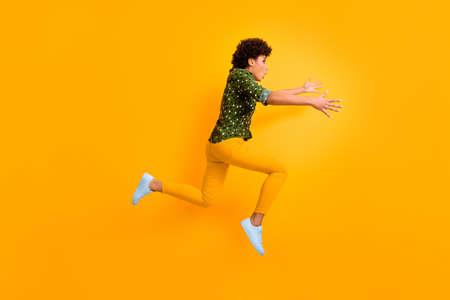Photo de profil complet du corps d'une dame frisée à la peau sombre et folle sautant haut se précipitant rapidement rencontrer l'aéroport de maman usure tardive chemise verte pointillée pantalon chaussures isolé fond de couleur jaune